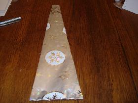 dans le papier cadeau, découper un rectangle de 9 cm x 35 cm<br /> le haut du sapin doit mesurer 2 cm ,pour cela, laisser 3,5 cm de chaque côté<br /> tracer et découper