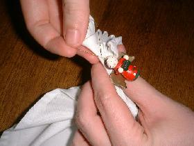 et nouer la figurine en bois pour éviter que la serviette ne s'ouvre.