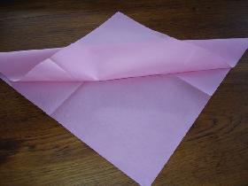 rabattre la pointe du pli dessus de la serviette vers le haut ( la pliure se trouve pratiquement au milieu<br /> bien marquer le pli