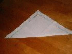 Prendre une serviette carrée et la plier en 2 pour obtenir un triangle
