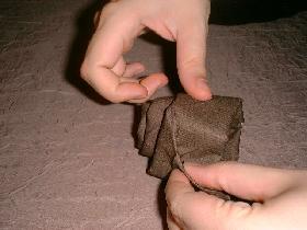 maintenir le tout en glissant l'extrémité dans un pli de la rosace