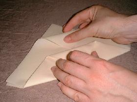 rabattre l'angle du haut (prendre une des feuilles) vers le bas et le passer sous le pli créé à l'étape précédente